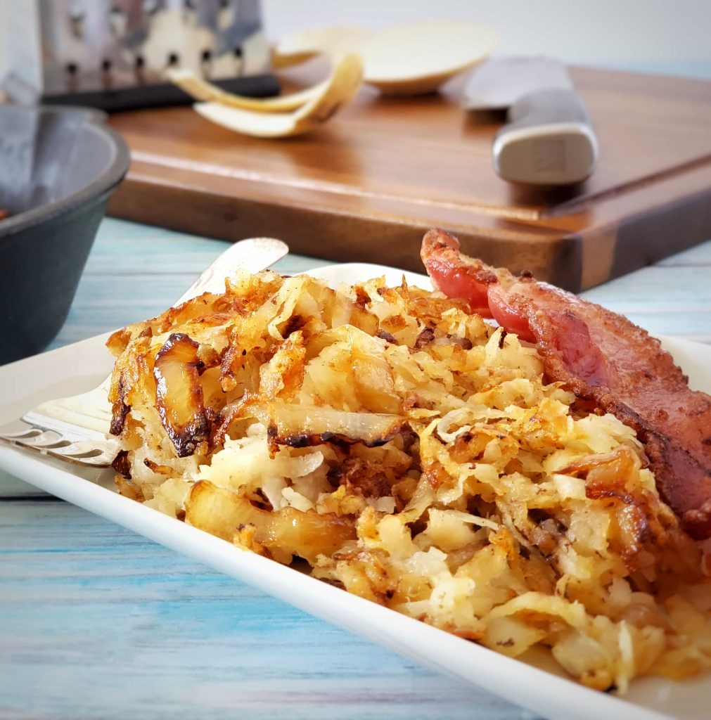 closeup photo of jicama hash browns on a plate with bacon